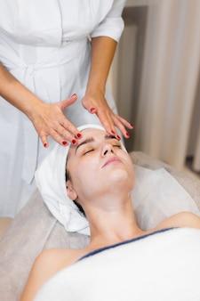 Kosmetyczka w salonie kosmetycznym spa nakłada krem na twarz klientki, dziewczyna leży na stole kosmetycznym