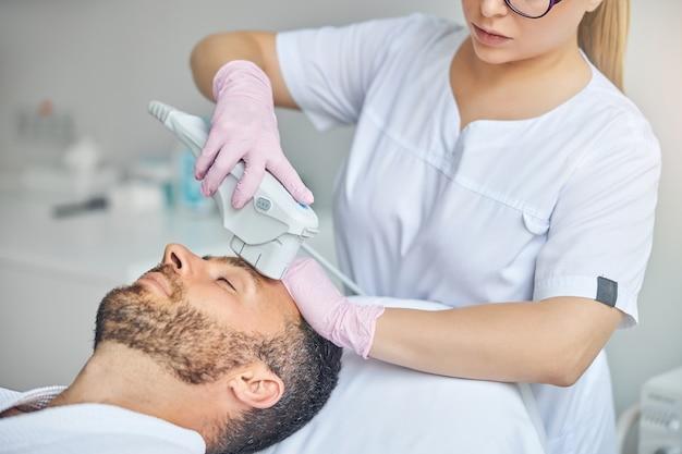 Kosmetyczka w sterylnych rękawiczkach lecząca męską skórę urządzeniem laserowym