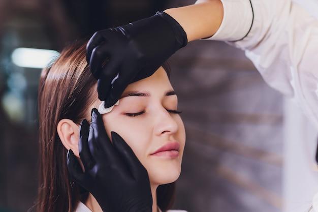 Kosmetyczka - wizażystka stosuje hennę malarską na uprzednio wyskubanych, designerskich, przyciętych brwiach w salonie kosmetycznym podczas korekcji sesji. profesjonalna pielęgnacja twarzy.