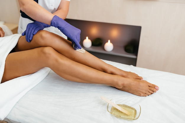 Kosmetyczka woskowanie nogi kobiety w salonie spa