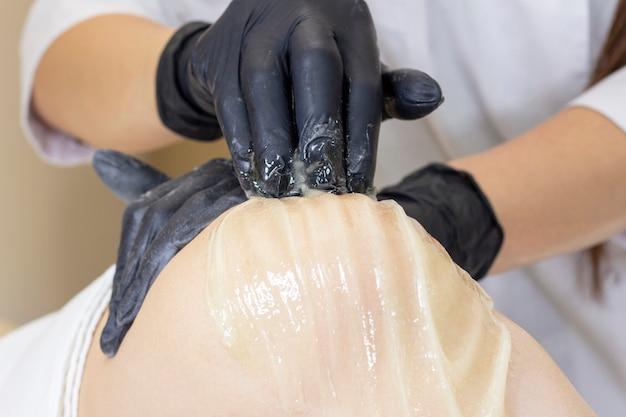 Kosmetyczka wykonująca depilację kobiecych nóg płynnym cukrem w centrum spa