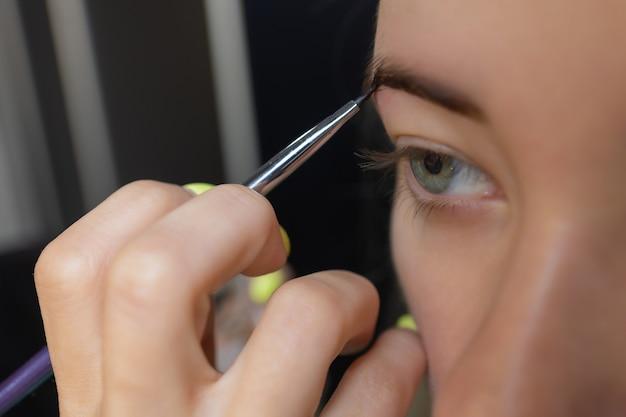 Kosmetyczka wykonująca depilację paskiem woskowym młoda kobieta brwi w centrum spa atrakcyjna kobieta...