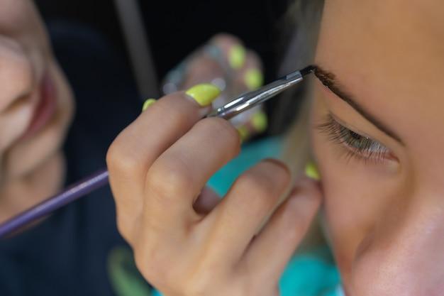 Kosmetyczka wykonująca depilację za pomocą paska woskowego brwi młodej kobiety w centrum spa. atrakcyjna kobieta coraz pielęgnacji twarzy w salonie piękności.