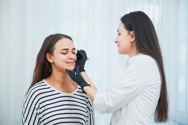 Kosmetyczka wykonująca korekcję brwi specjalnymi instrumentami. młoda kobieta robi zabiegu twarzy uroda.