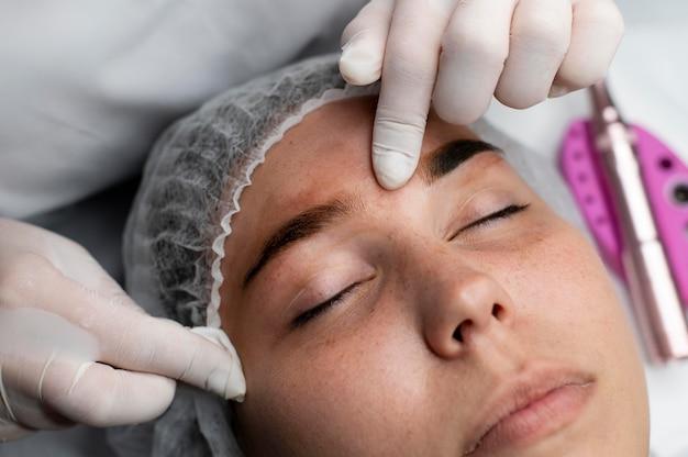 Kosmetyczka wykonująca zabieg microblading na kobiecie
