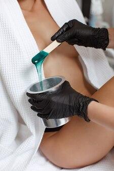 Kosmetyczka wykonuje depilację młodej kobiety