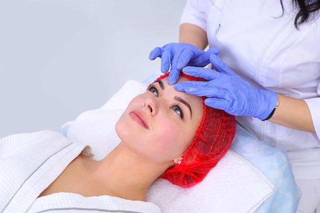 Kosmetyczka wykonuje oczyszczająco-złuszczający zabieg na twarz dla pięknej dziewczyny. salon piękności.