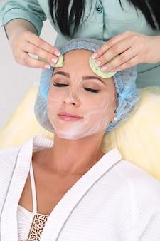 Kosmetyczka wykonuje oczyszczająco-złuszczający zabieg na twarz dla pięknej dziewczyny