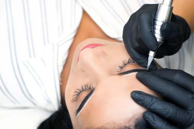 Kosmetyczka wykonuje permanentny makijaż brwi na twarzy pięknej młodej kobiety