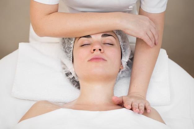 Kosmetyczka wykonuje profesjonalny masaż twarzy, szyi i ramion dla młodej dziewczyny w salonie spa.