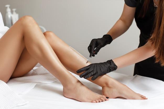 Kosmetyczka wykonuje woskiem depilację młodej kobiety na nodze