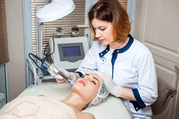 Kosmetyczka wykonuje zabieg odmładzania skóry twarzy specjalnym urządzeniem w gabinecie kosmetycznym