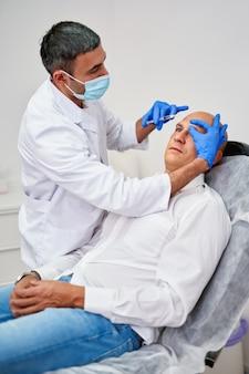Kosmetyczka wykonuje zastrzyk w twarz pacjenta