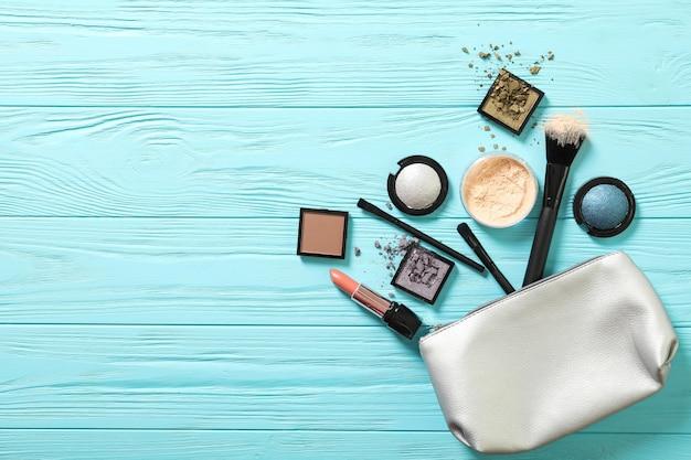 Kosmetyczka z dekoracyjnymi kosmetykami na niebieskim tle. miejsce na tekst