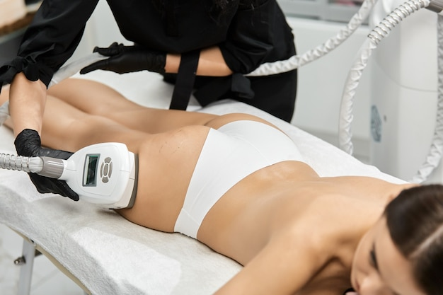 Kosmetyczka za pomocą lasera na nogi kobiety w salonie spa
