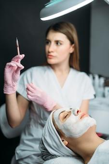 Kosmetyczka ze strzykawką w rękach, zastrzyk botoksu