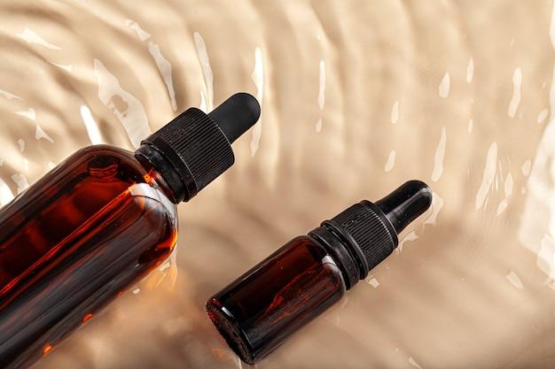 Kosmetyczna butelka z pipetą w falistej wodzie, widok z góry