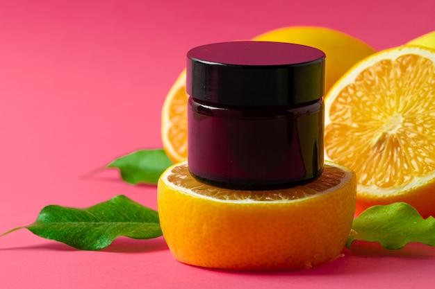 Kosmetyczna butelka z plasterkami owoców cytrusowych na jasnym różu