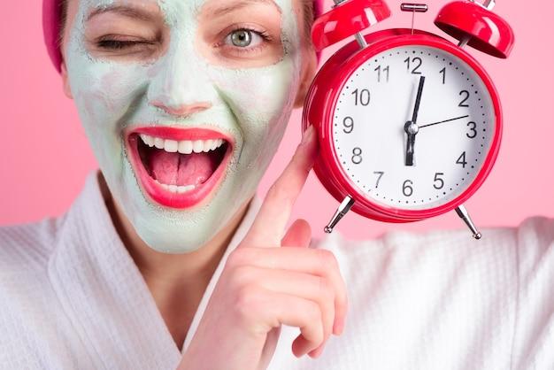 Kosmetyczna maska do twarzy spa zabiegi kosmetyczne kobieta z kosmetyczną maską na twarzy trzyma zegar wellness