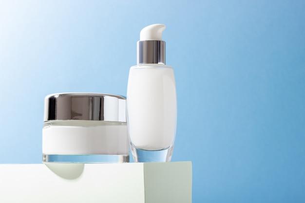 Kosmetyczne szklane butelki z kremem i maską na wybiegu z twardymi cieniami. koncepcja salonu kosmetycznego i kosmetyków naturalnych.