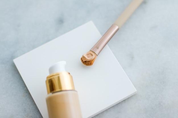 Kosmetyczny branding glamour i koncepcja pielęgnacji skóry podkład do makijażu i pędzel do konturowania na mar...