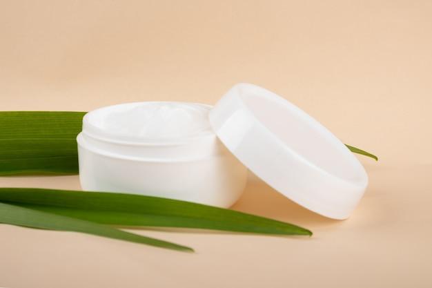 Kosmetyczny krem i zielony liść na beżowym tle. ochrona skóry.