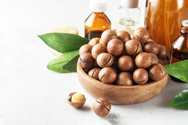 Kosmetyczny olej z orzechów makadamia na szarym betonowym stole.