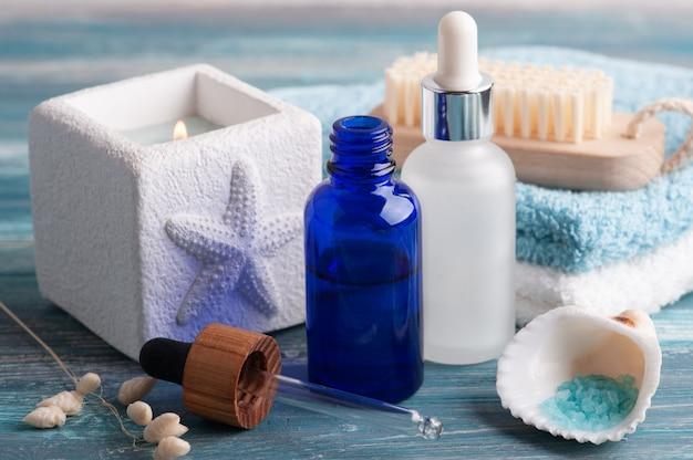 Kosmetyczny olejek eteryczny na podłoże drewniane. naturalne organiczne spa z ekologicznym opakowaniem i solą morską