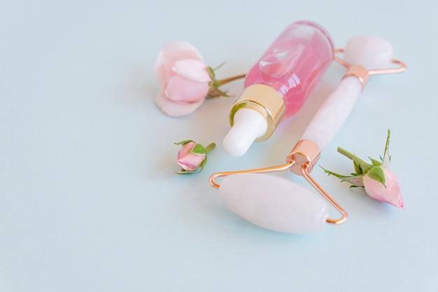 Kosmetyczny olejek eteryczny z róży i różany kwarcowy masażer do twarzy kamień gua-sha do masażu twarzy w domu. koncepcja pielęgnacji skóry i twarzy.