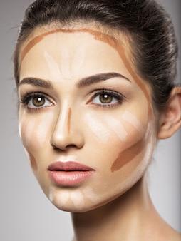 Kosmetyczny podkład tonalny do makijażu nakładany jest na twarz kobiety. koncepcja zabiegów kosmetycznych. dziewczyna robi makijaż.