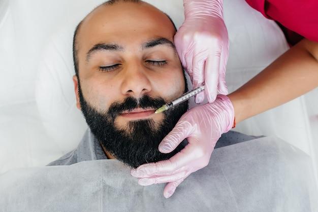 Kosmetyczny zabieg powiększania ust i usuwania zmarszczek u brodatego mężczyzny. kosmetyka.