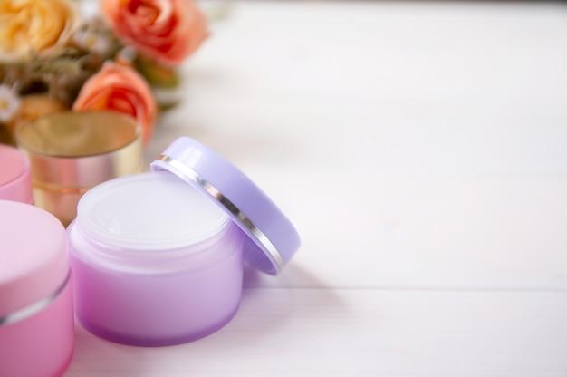 Kosmetyk i produkt do pielęgnacji skóry i kwiat na białym stole drewna