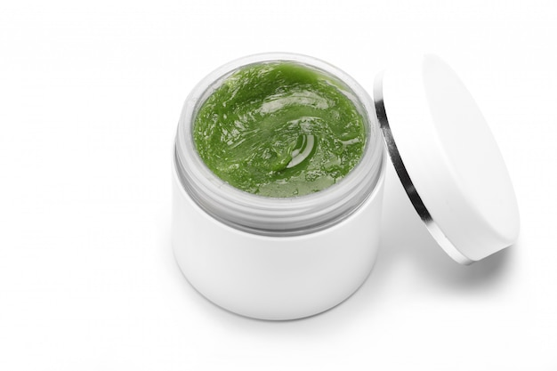 Kosmetyk naturalny krem do twarzy i ciała zielony w białym pojemniku, słoik pojedynczo na białym stole. kopia przestrzeń