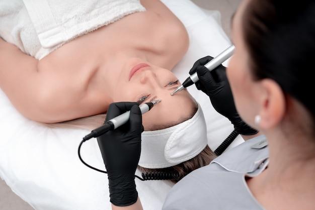Kosmetyka. piękna kobieta w klinice spa otrzymujących stymulujące elektryczne leczenie twarzy od terapeuty. zbliżenie młodej twarzy kobiety podczas terapii mikroprądowej