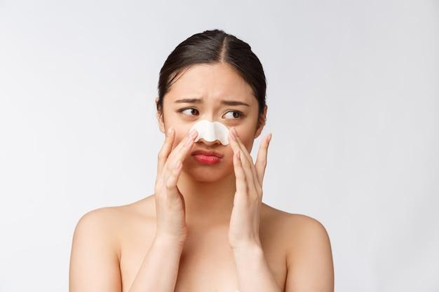 Kosmetyka. portret pięknej modelki azjatyckich kobiet z maską na nosie. zbliżenie zdrowa młoda kobieta z czystą miękką skórą i świeżym naturalnym makijażem.