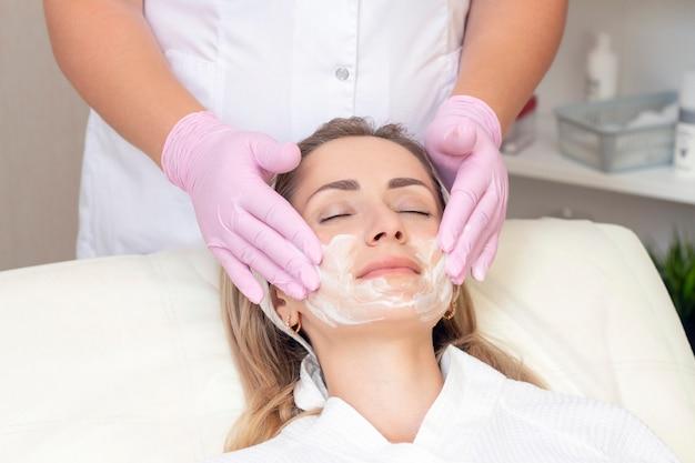 Kosmetyka. zamknij się obraz ślicznej młodej kobiety z zamkniętymi oczami otrzymującej procedurę oczyszczania twarzy w salonie kosmetycznym.