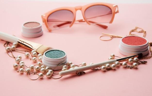 Kosmetyki damskie akcesoria biżuteria okulary różowe tło.