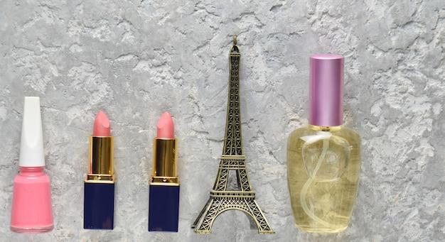 Kosmetyki damskie z paryża. dwie różowe pomadki, butelka perfum, lakier do paznokci, statuetka wieży eiffla. widok z góry.