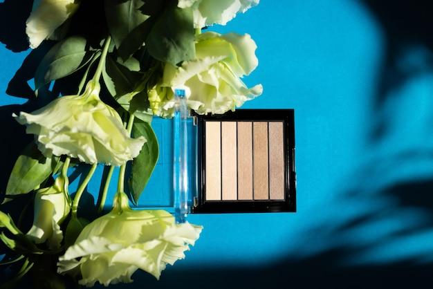 Kosmetyki dekoracyjne. beżowy cień do powiek na niebieskim tle. dekoracja z kwiatów róży