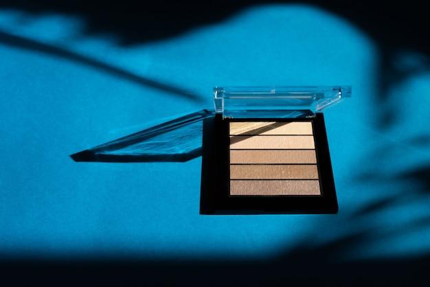 Kosmetyki dekoracyjne. beżowy cień do powiek na niebieskim tle