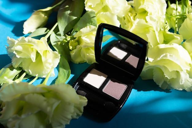 Kosmetyki dekoracyjne. cienie beżu na niebieskim tle. dekoracja z kwiatów róży