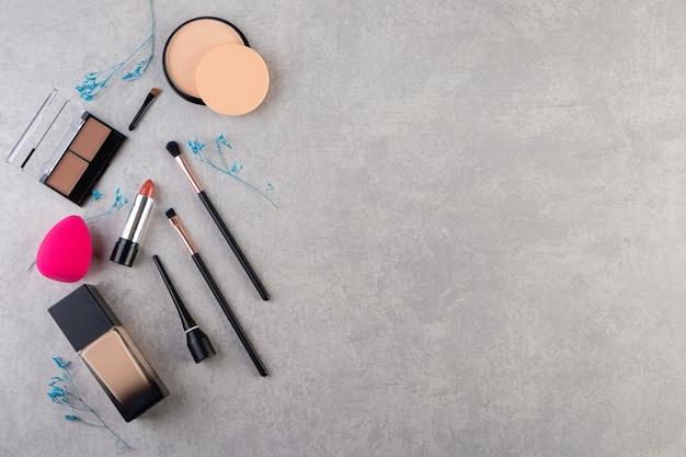 Kosmetyki dekoracyjne i pędzle do makijażu umieszczone na kamiennym stole.
