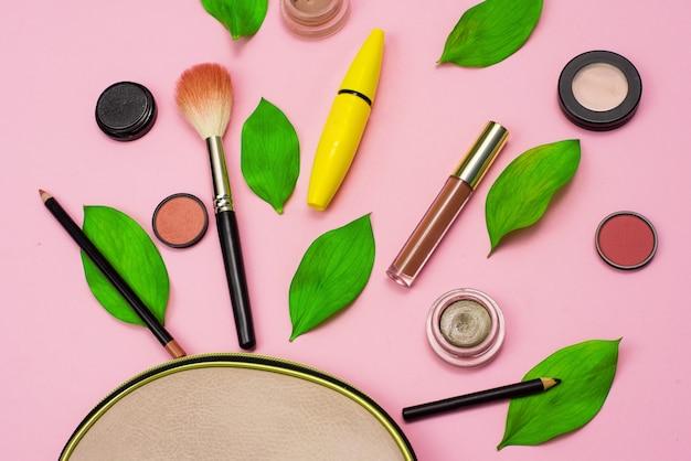 Kosmetyki dekoracyjne na różowym tle obok beżowej kosmetyczki i zielonych świeżych liści. koncepcja kosmetyków naturalnych do makijażu