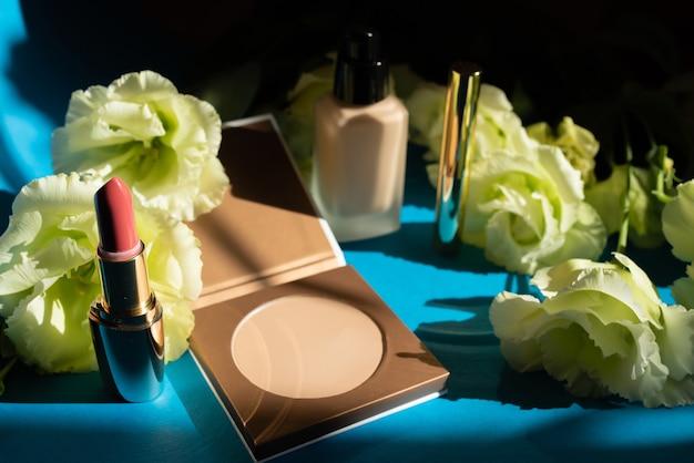 Kosmetyki dekoracyjne. puder do twarzy na niebieskim tle. dekoracja z kwiatów róży