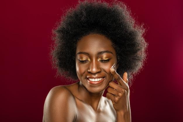 Kosmetyki dla młodej skóry. twarz wesołej młodej kobiety uśmiechniętej podczas nakładania kremu na jej skórę