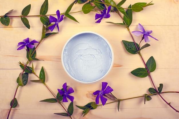 Kosmetyki do ciała, uroda, peeling do pielęgnacji skóry na drewnianym tle z gałęzi fioletowych kwiatów