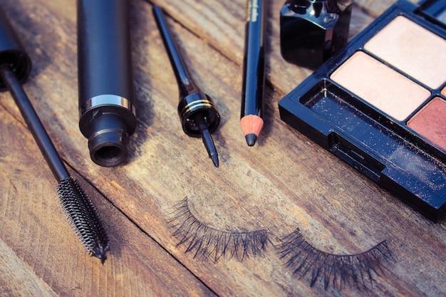Kosmetyki do oczu: kredka, tusz do rzęs, eyeliner, sztuczne rzęsy i cień do powiek. stonowany obraz.