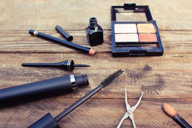 Kosmetyki do oczu: ołówek, tusz do rzęs, eyeliner, sztuczne rzęsy i cień do powiek. stonowany obraz.