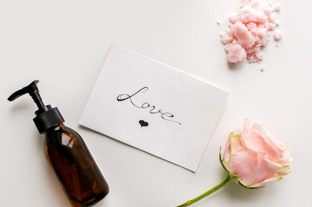 Kosmetyki do pielęgnacji ciała, kwiat i biała karta z napisem miłość