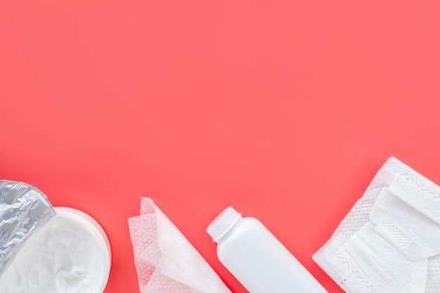 Kosmetyki do pielęgnacji niemowląt na różowym tle, płaskie mieszkanie, widok z góry, miejsce na tekst, makieta. modne tło, higiena noworodków.